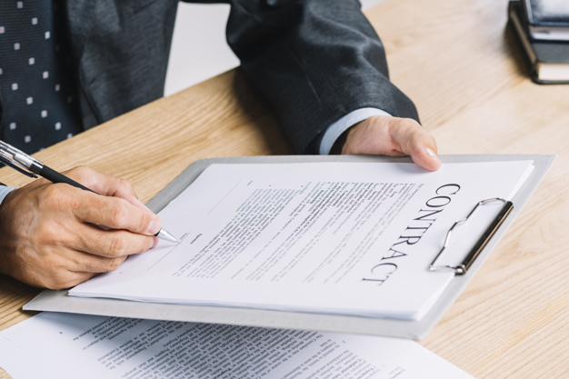 hombre-que-firma-documento-contrato-adjunta-portapapeles-mesa-madera_23-2147898343